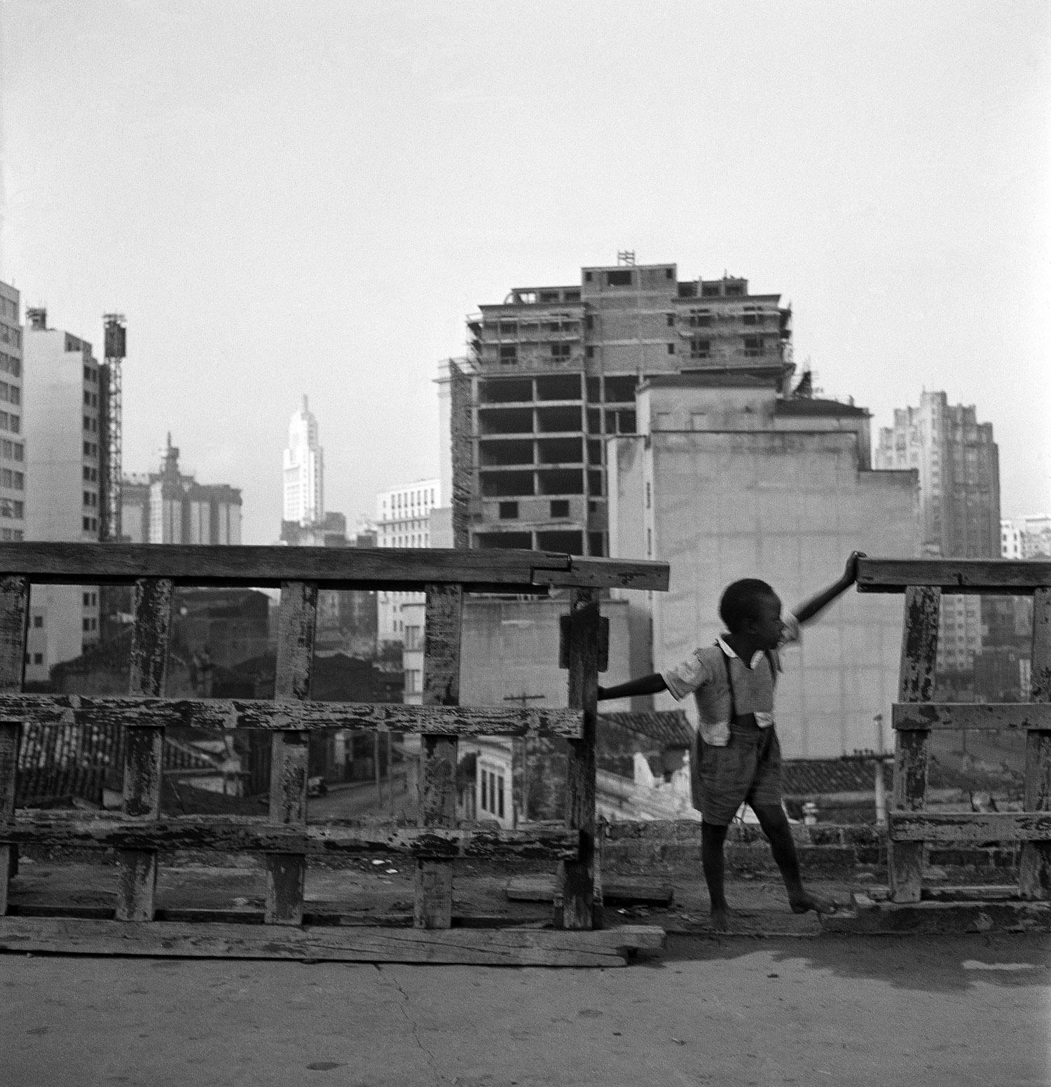 Menino no telhado com a cidade de São Paulo ao fundo
