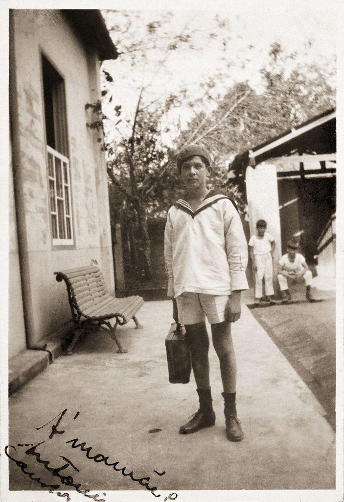 Antonio Candido no quintal da casa da Rua Sergipe, saindo para o Ginásio Municipal de Poços de Caldas, observado pelos irmãos Roberto e Miguel, ao fundo. Poços de Caldas, 1930 / Arquivo do IEB-USP