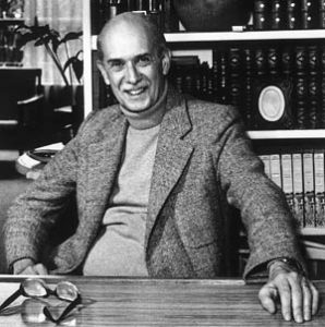 O crítico literário Antonio Candido sentado diante de uma estante com livros. Óculos e mão esquerda apoiada na mesa.