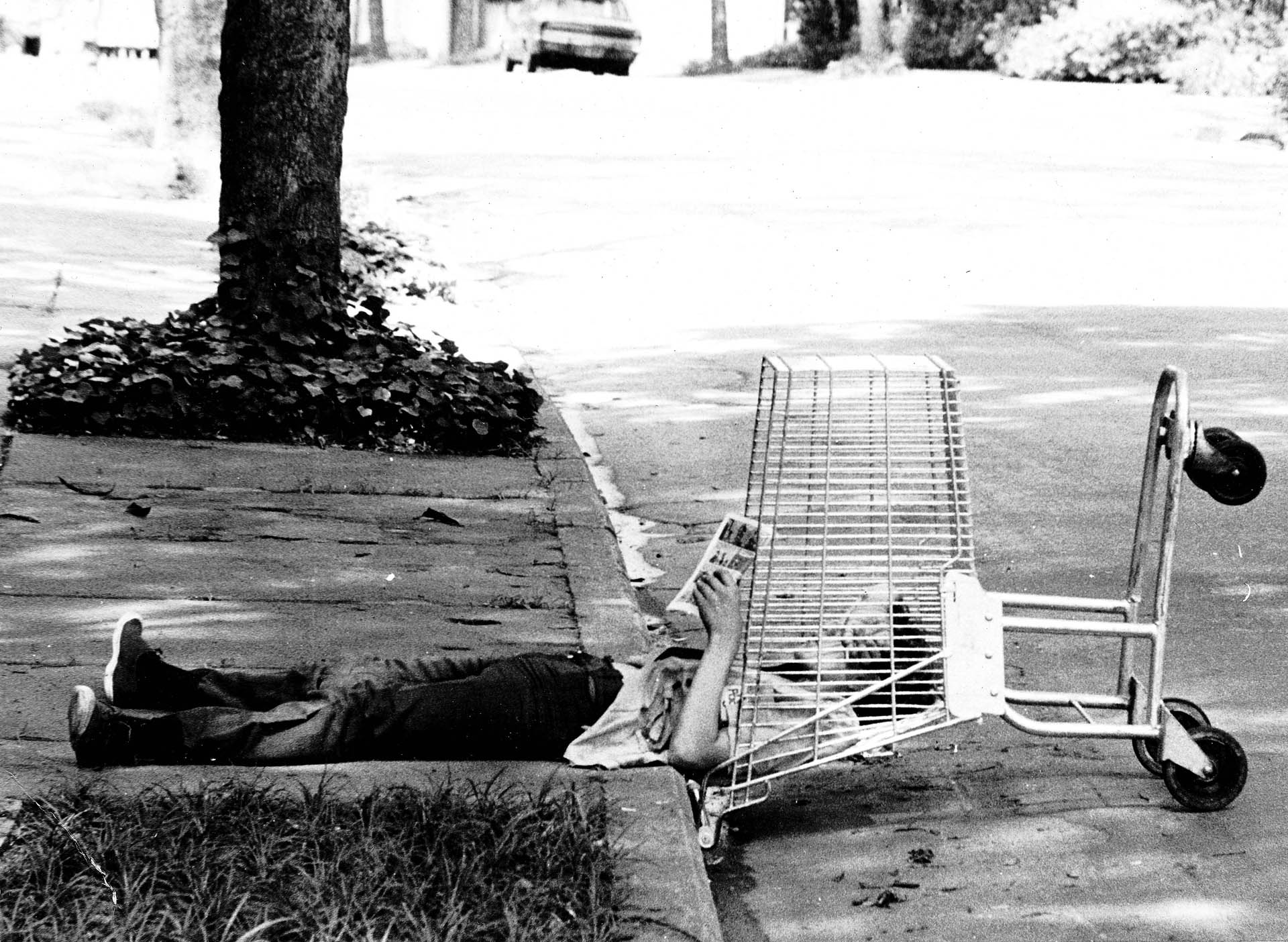 Fotografia de homem deitado na calçada. A parte de cima do corpo está apoiada num carrinho de compras de supermercado.