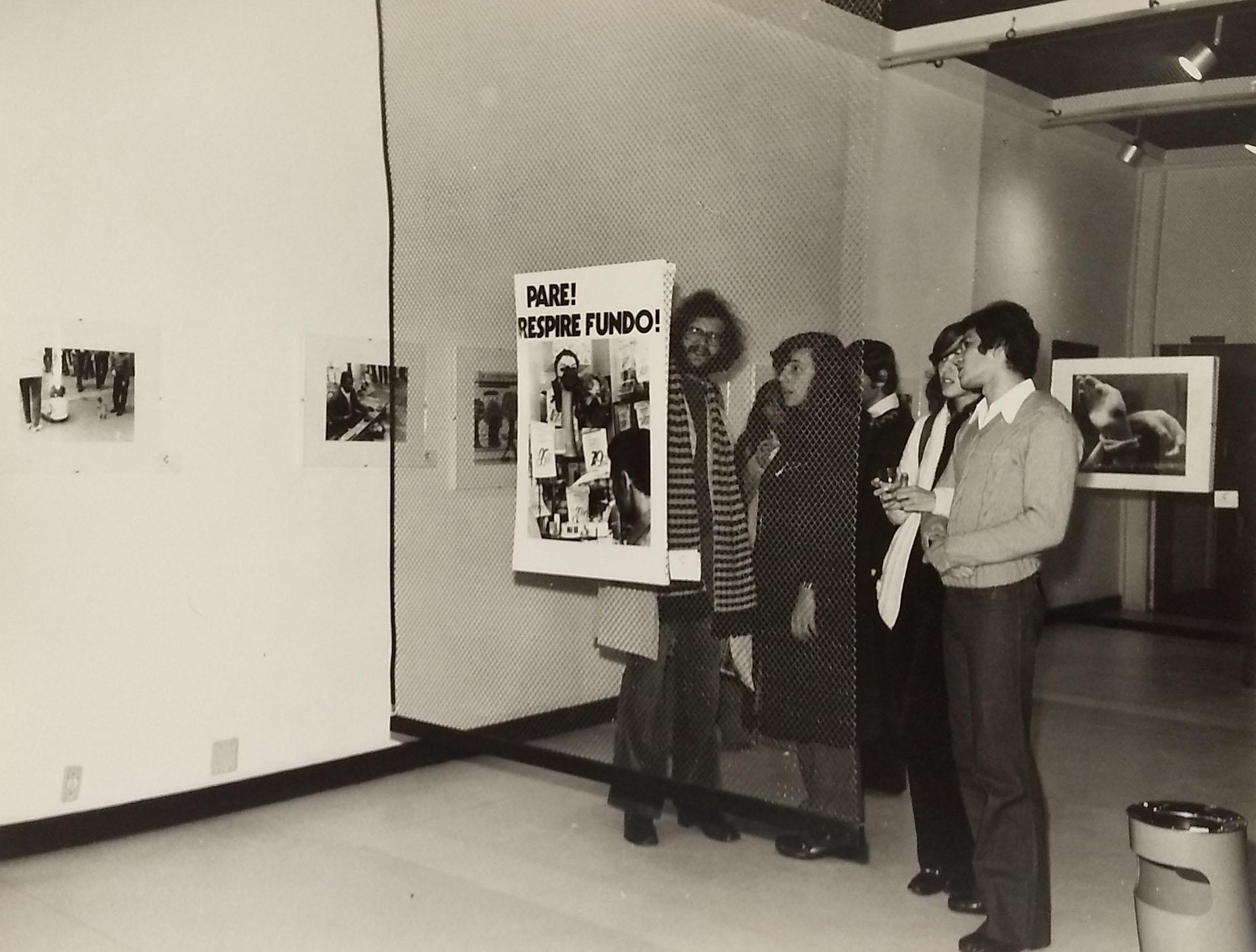 Grupo de pessoas observa fotografia afixada em suporte em uma sala com outras fotos expostas