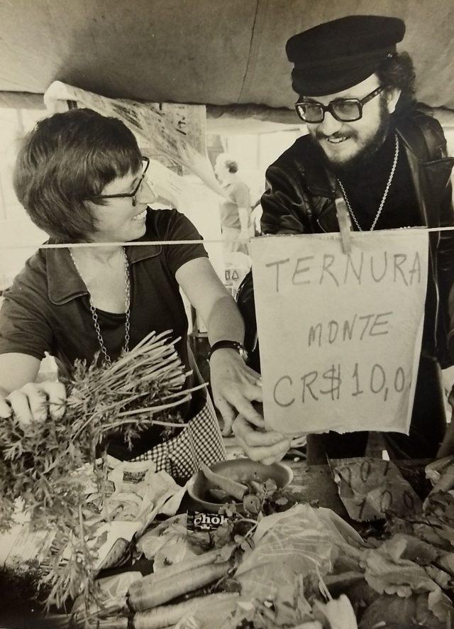 """Banca de feira com cenouras e folhagens, um cartaz pendurado com os dizeres """"Ternura // monte // CR$10,00"""". Stefania Bril e Olney Kruse sorriem e se olham"""