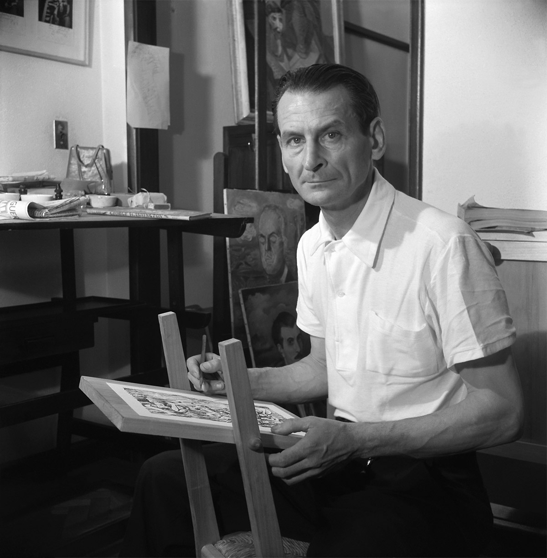 O artista olha para a câmera. Está sentado, desenhando sobre uma pequena mesa.. Veste camisa social clara, de mangas curtas.