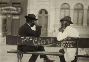 """Os dois homens estão sentados e aparecem de perfil. Estão de terno e chapéu. O banco é visto por trás e tem uma propaganda de """"Calçado Clark"""" no encosto."""