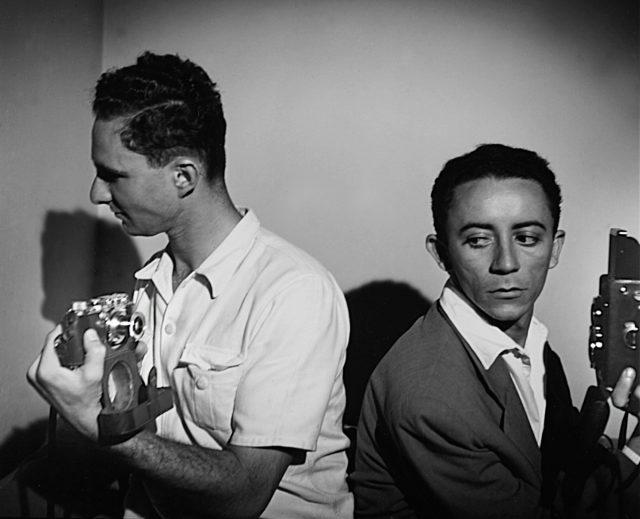 Retrato dos dois fotógrafos da cintura para cima. Eles seguram câmeras e estão de costas um para o outro. Farkas está à esquerda, Medeiros à direita.