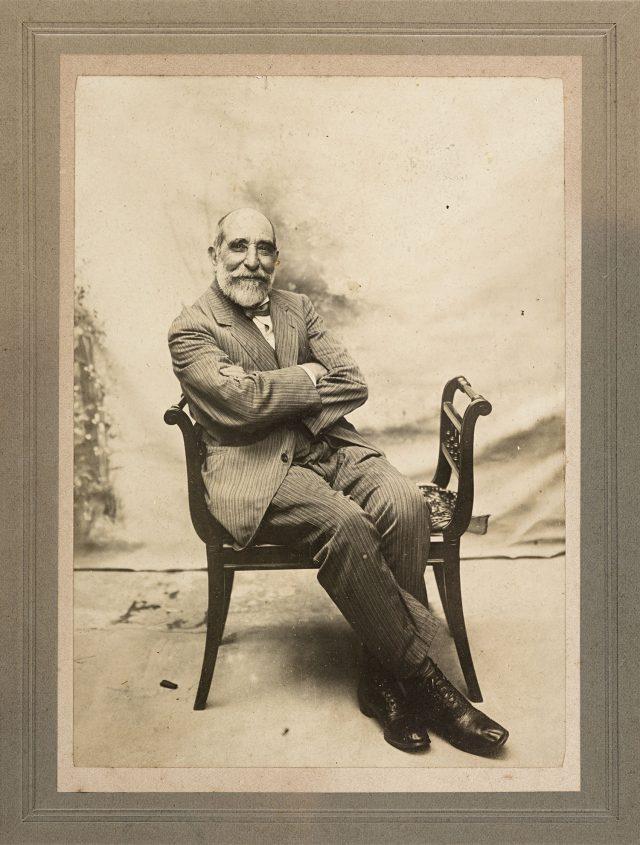 O fotógrafo está sorridente, de braços cruzados, sentado num banco. Ele usa óculos, tem barba e está vestindo um terno de tecido listrado.