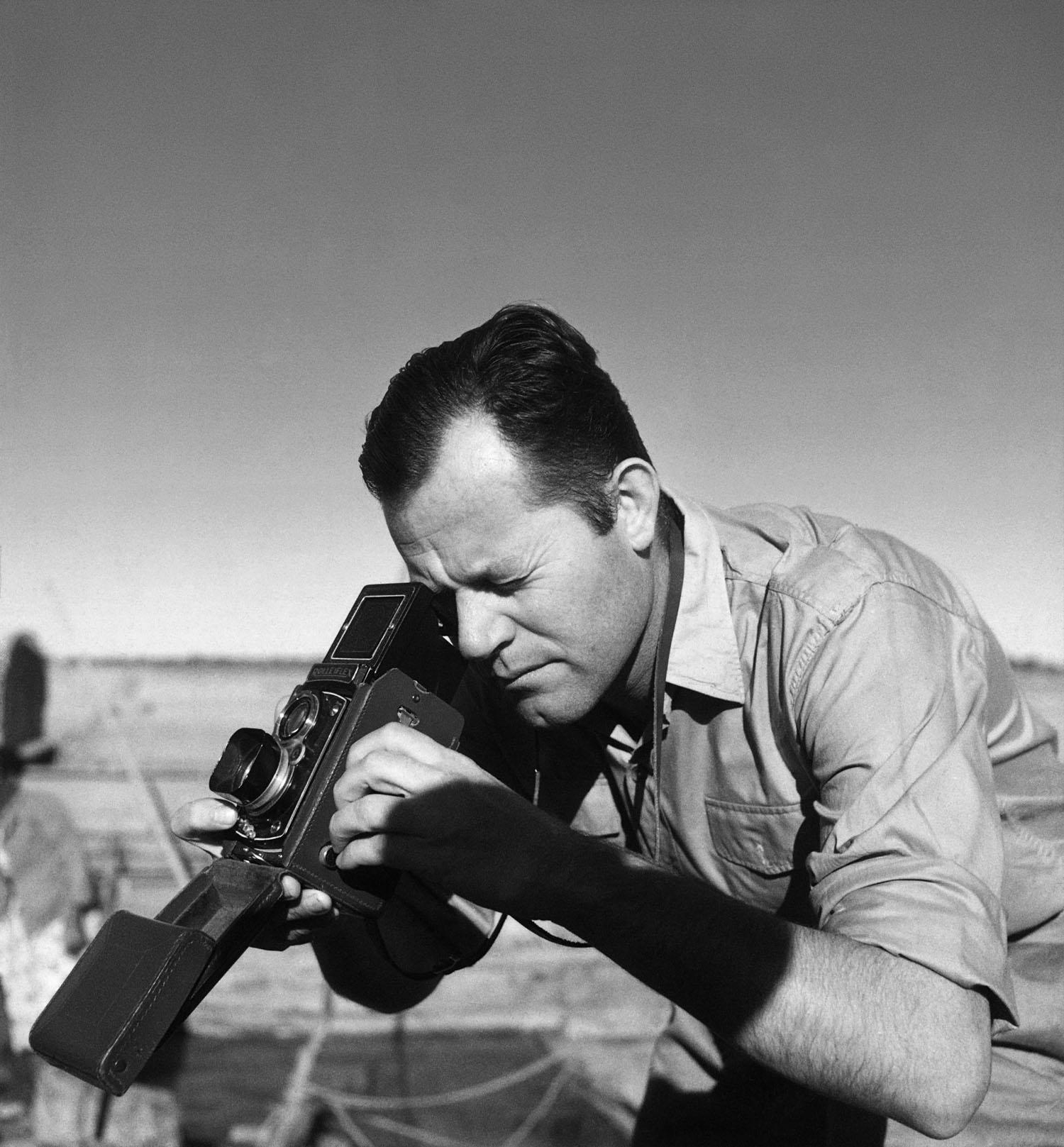O fotógrafo está inclinado para frente, segurando uma câmera e olhando através do visor do equipamento