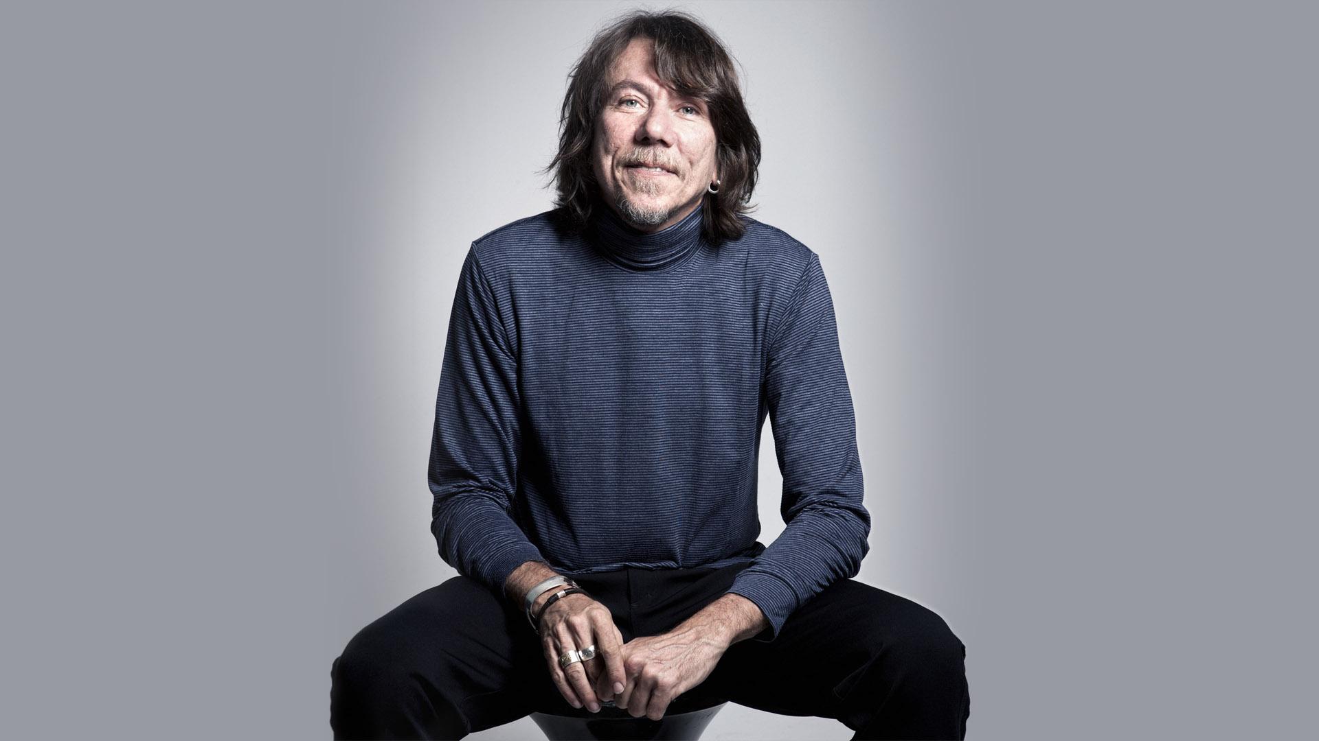 O músico está sentado num banco. Ele olha para a câmera e veste blusa cinza de manga comprida e calça preta