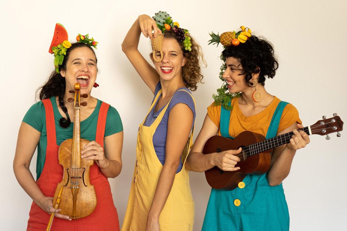 Três mulheres sorridentes com roupas de cores vibrantes e frutas na cabeça