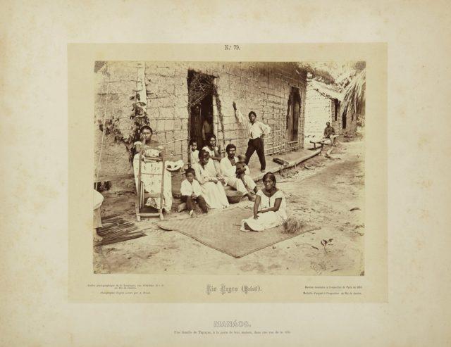 """""""Manaus. Uma família de Tapuias, na porta de sua casa, em uma rua da cidade"""". Rio Negro, Amazônia, 1867-68. Imagem publicada pela Casa Leuzinger em 1869, no conjunto <em>Resultado de uma expedição fotográfica pelo Solimões ou Alto Amazonas e pelo rio Negro</em>. Fotografia de Albert Frisch / Acervo IMS"""