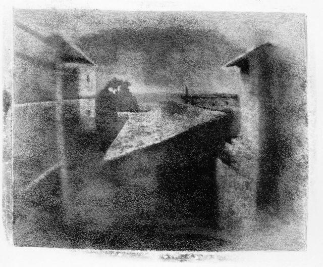Vista de uma janela em Gras, residência de em Chalon-sur-Saône, 1826. Mais antiga imagem fotográfica que chegou à atualidade, obtida por um dos inventores da daguerreotipia em uma placa de estanho, sensibilizada com betume da judeia, depois de oito horas de exposição à luz solar. Fotografia de Nicéphore Niépce/ Museu Nicéphore Niépce, Chalon-sur-Saône (França)