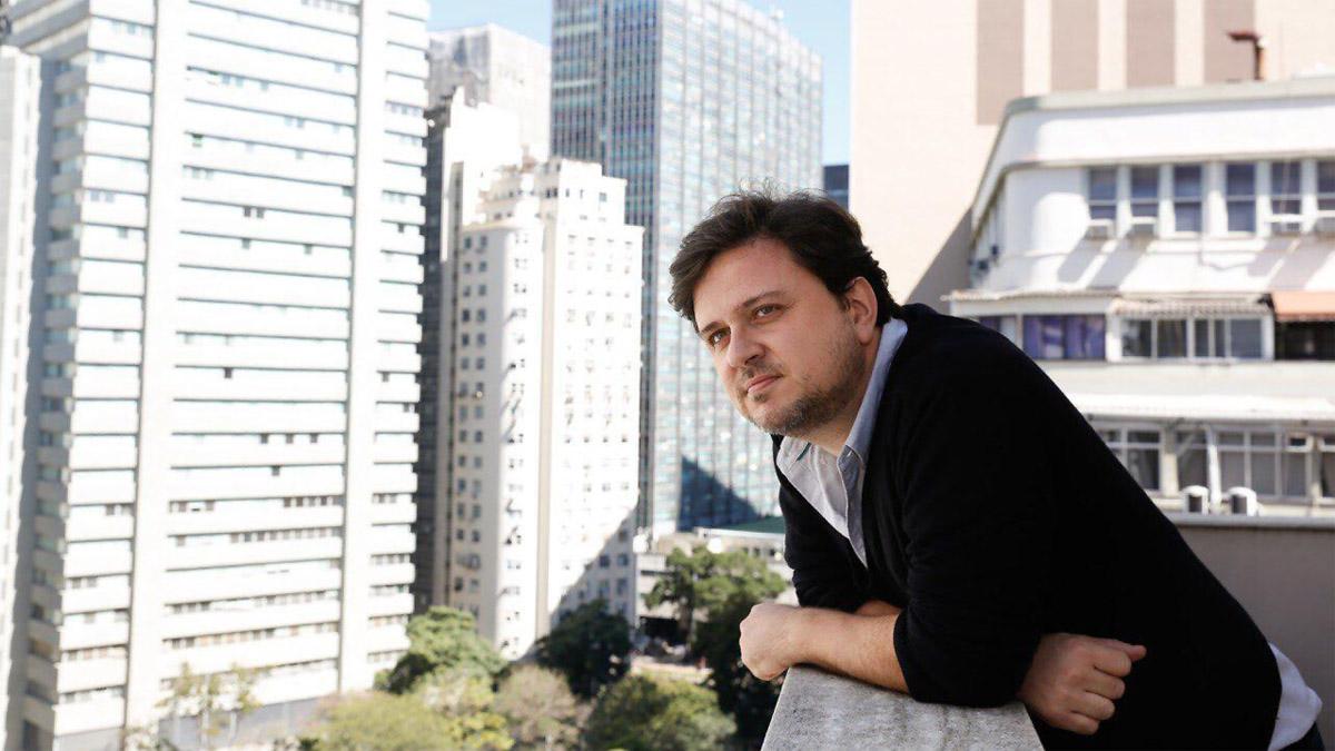 Homem apoiado num peitoril com prédios ao fundo